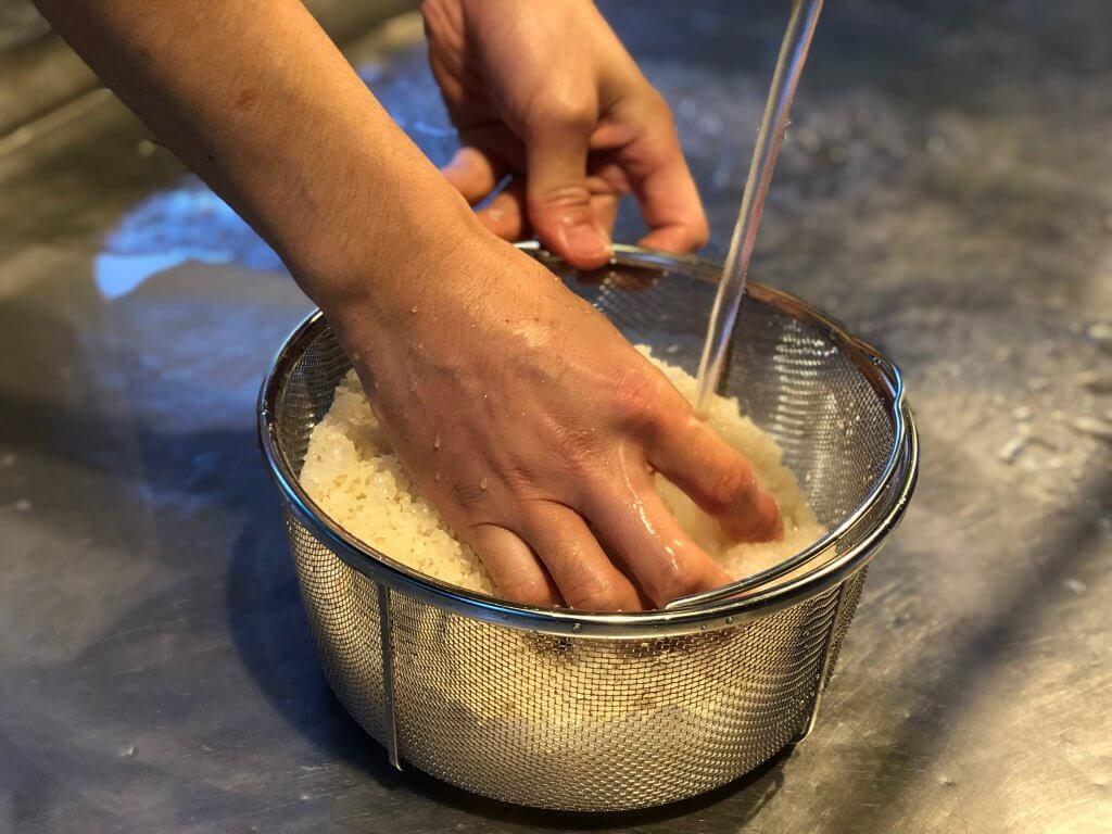 炊事場で米とぎ