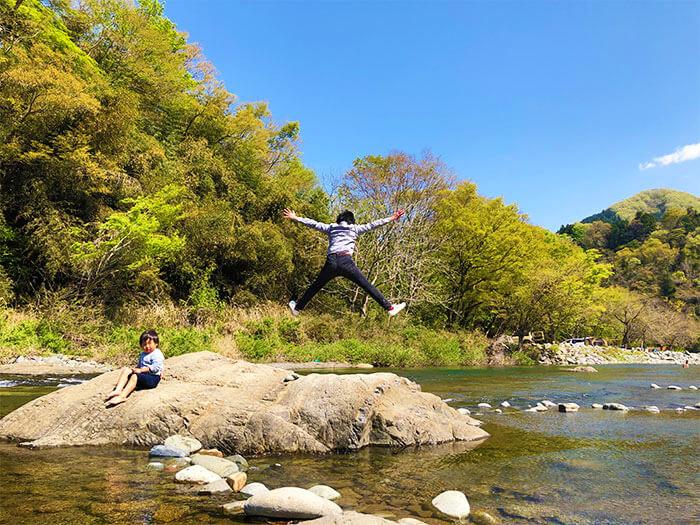 青野原オートキャンプ場を流れる道志川で遊ぶ大人
